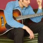 04 - TRAVIS PROMO 3 Sitting w guitar pulling on hair